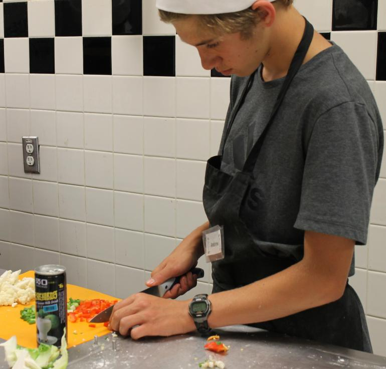 Teen in kitchen chopping vegetables