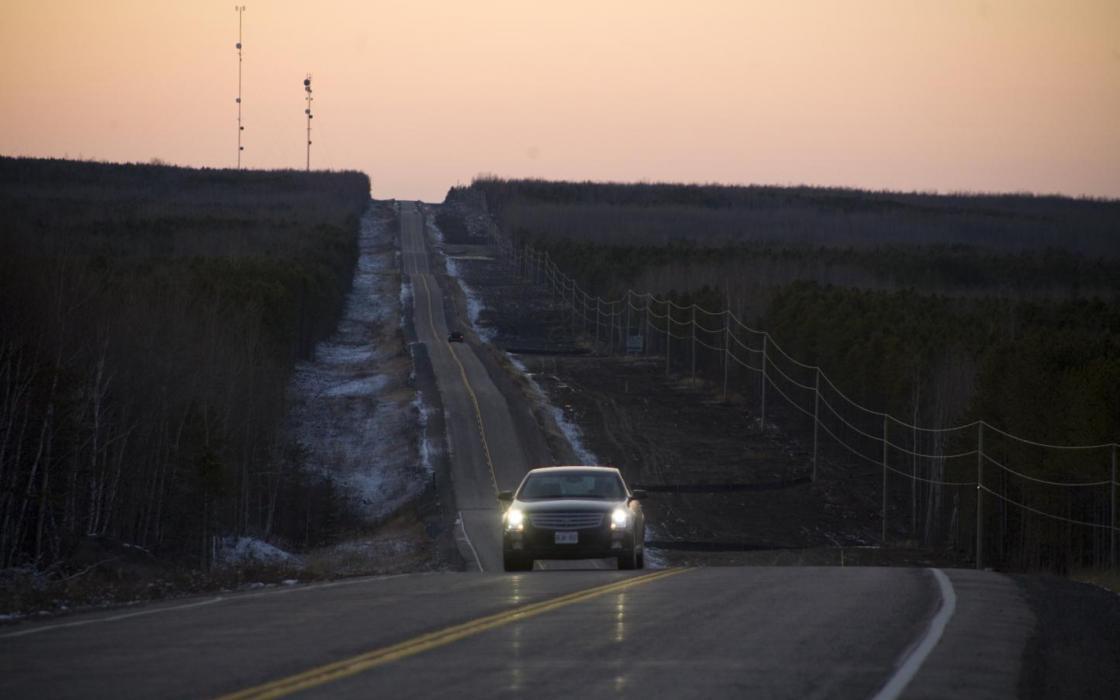 Long straight road driving towards Red Lake at sunset