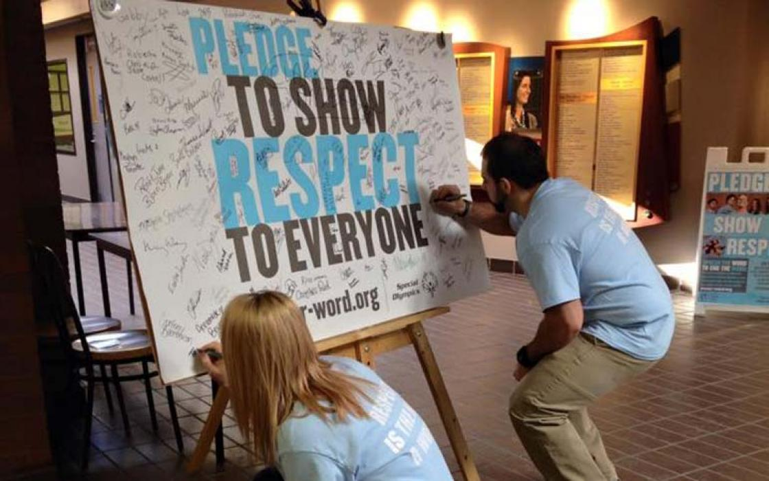 photo - students signing a pledge to show respect to everyone