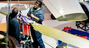 photo - Aircraft Maintenance students removing a helicopter blade