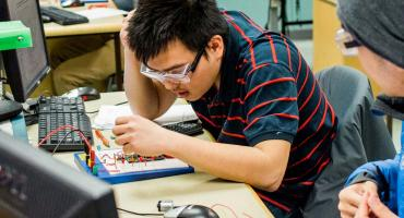 banner photo - international student working in electronics lab