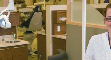 banner photo - smiling female student in our dental lab