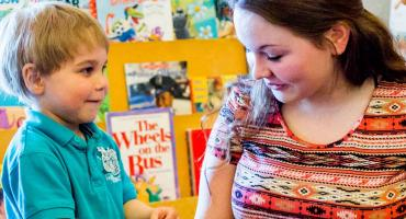 banner photo - student working with 2 children in our ECE Lab