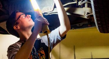 photo - Automotive student inspecting underside of a vehicle