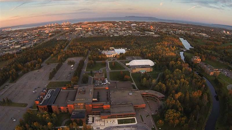 Drone aerial photo of Thunder Bay Main Campus Shuniah Building at sunset with Sleeping Giant & Lake Superior in background